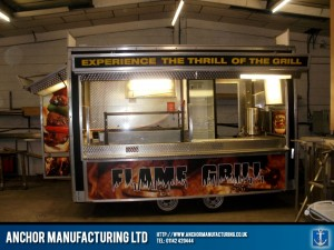 A fabricated stainless steel food trailer with integrated mobile kitchen.